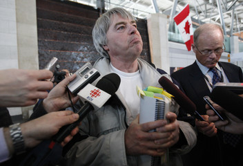 Robert Latimer speaks with journalists at the Ottawa International Airport