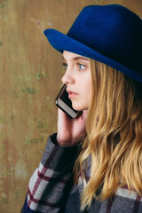 charming young woman in hat speaking on mobile phone