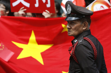 A policeman keeps guard in front of supporters before start of Beijing 2008 Olympic Torch Relay through Bangkok