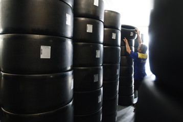 An employee of French tyre manufacturer Michelin moves tyre stocked on the racing circuit before Le Mans 24 Hours endurance race in Le Mans
