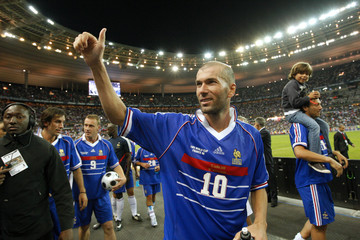 France's Zinedine Zidane waves to supporters at the end of an exhibition soccer match at the Stade de France in Saint-Denis