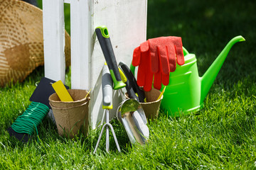 Gardening tools and a straw hat on the grass in the garden.