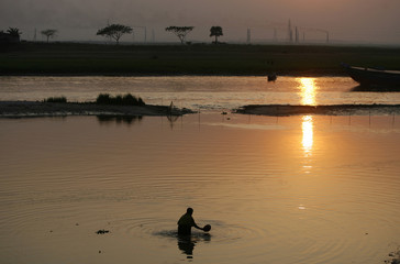 A woman baths in a river as brick kilns are seen in the background during sunset in Dhaka