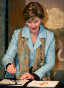 U.S. first lady Laura Bush concentrates on her brush stroke during a calligraphy workshop inside a r..