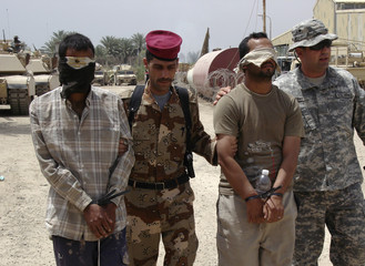 U.S. and Iraqi soldiers escort blindfolded detainees who were arrested during a raid in Yussifiya