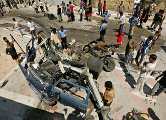 Palestinians examine car hit by missile fired by Israeli aircraft in Beit Hanoun, northern Gaza Strip