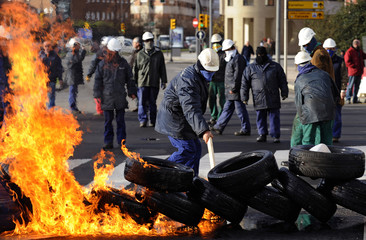 A shipyard worker sets up a barricade during a protest in Gijon