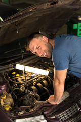 Meсhanic smiling and looking in camera while doing engine diagnostics of old car.