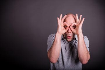 Mann mit grauem Poloshirt formt lachend mit seinen Fingern eine Brille, schaut erstaunt dabei Wall mural