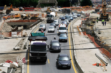 Vehicles drive by as construction crew work in Madrid