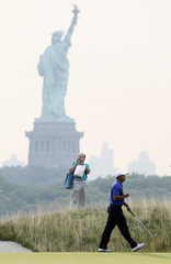 New York's Statue of Liberty is seen in the background as Tiger Woods of the U.S. walks off the second green during The Barclays Pro-Am golf tournament