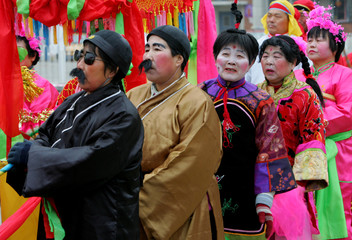 Chinese women stand in a line before a performance in Beijing