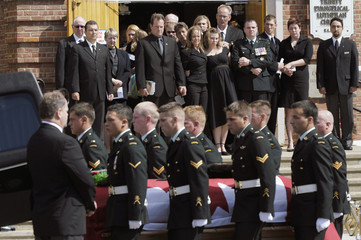 Friends and family of Weibe watch as Military pall bearers load casket into hearse following funeral in Edmonton