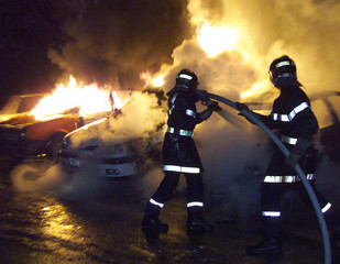 FIREMEN EXTINGUISH BURNING CARS IN STRASBOURG, FRANCE.