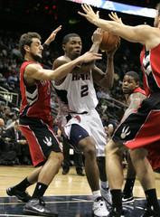 Atlanta Hawks guard Joe Johnson drives between Toronto Raptors guard Marco Belinelli, Amir Johnson and center Andrea Bargnani, in the first half of NBA basketball action in Atlanta
