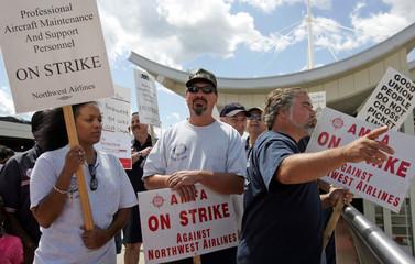 Northwest Airlines striking workers watch repacement workers do strikers jobs.