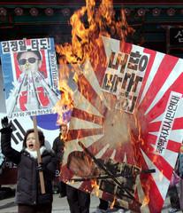 South Korean protesters burn a sign denouncing the Japanese ambassador to South Korea at a ...