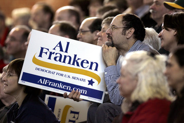 A man listens to comedian Al Franken speaking at a rally in St Louis Park