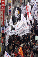 SOUTH KOREAN WORKERS MARCH DURING A DEMONSTRATION IN SEOUL.
