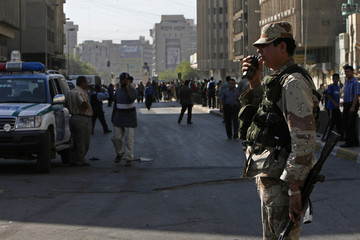A soldier stands guard after two bombs exploded in a market in central Baghdad