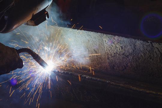 Worker welding steel by MIG/MAG weld (Argon welding) in industrial factory .