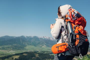 Woman backpacker traveler drinks hot tea on the mountain top