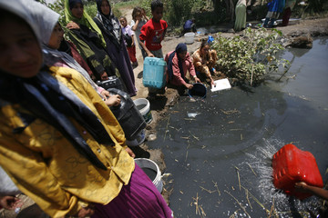 Residents fill containers with water from a polluted pond in El Salhia village in El Faiyum