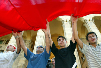 Protesters hold giant flag during an opposition rally outside parliament in central Tbilisi