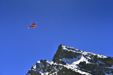 Rescue helicopter over the Tatra mountain peak.