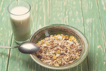 Bowl of oat flakes and glass of milk, on wooden background. Toned.