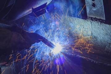 Worker welding steel by MIG/MAG weld (Argon welding) in industrial factory.