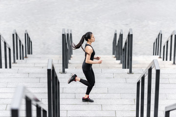 Side view of young fitness woman in sportswear training on stadium stairs