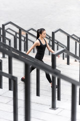 Young sporty asian woman in sportswear jogging on stadium stairs