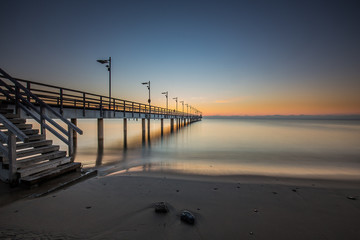 Wooden pier in Mechelinki. Small fishing village in Poland. Amazing Sunrise at the beach