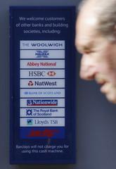 A man walks past a cash machine displaying bank names in Loughborough