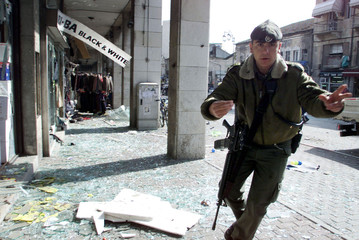 AN ISRAELI SOLDIER GUARDS THE SCENE AFTER A SUICIDE BOMBING IN CENTRALJERUSALEM.
