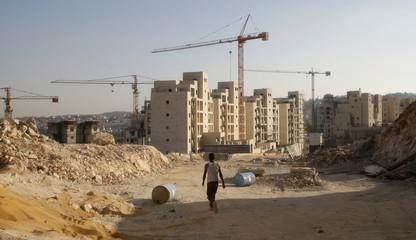 Palestinian labourer walks near buildings under construction at settlement near Jerusalem