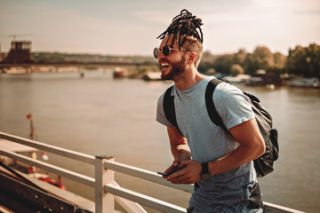 Man with dreadlocks using phone by the river