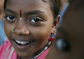 An Indian tribal girl reacts to the camera in a small hamlet beside a Christian school on the outskirts of Jeypore village