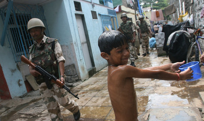 Paramilitary troops patrol a residential area as a boy takes a bath next to Arthur Road jail in Mumbai