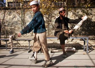 AFGHAN MEN TRY THEIR ARTIFICIAL LEG IN HOSPITAL IN KABUL.