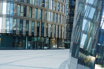 Entrance of modern glass office building, busy city center reflected on its outer walls