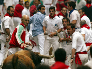 Revellers run in front of a fighting bull on Estafeta Street in central Pamplona during the fifth bu..