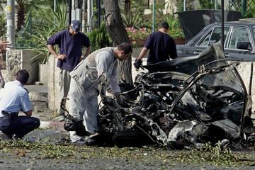 ISRAELI POLICE SAPPERS EXAMINE CAR BOMB SITE IN JERUSALEM.