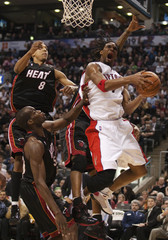 Toronto Raptors Bosh goes to basket against Miami Heat Anthony and Moon during their NBA basketball game in Toronto