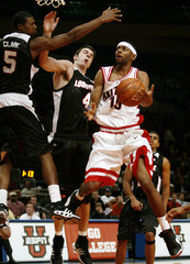 Wildcats Shakur drives to the hoop past Cardinals Clark and Padgett in second half of their game in New York
