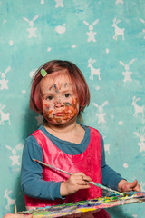 Portrait of a child stained with paints