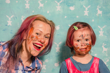 Mom and the child draw paints of each other's faces.
