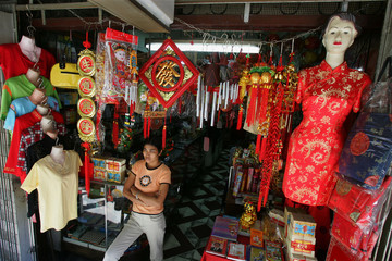 Philippine worker waits for customers in front of a Chinese store at Manila's Chinatown