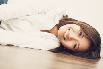 Happy Asian businesswoman lying on floor